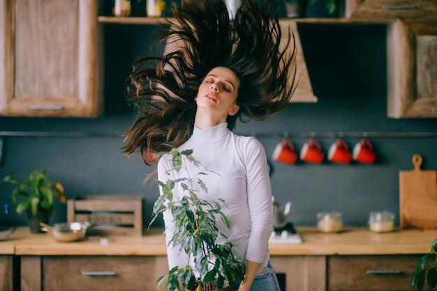 Крытый образ жизни портрет красивой молодой девушки с разбросанными волосами и наклонной головой, держа горшок с цветком.