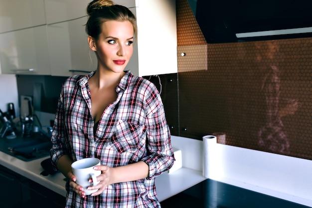 かなりブロンドの女性の屋内ライフスタイルの肖像画はリラックスして彼女の朝の時間を楽しんで、キッチンでポーズをとって、居心地の良い格子縞のシャツ、ビンテージフィルムの柔らかい色を着ています。おいしいコーヒーを飲みます。