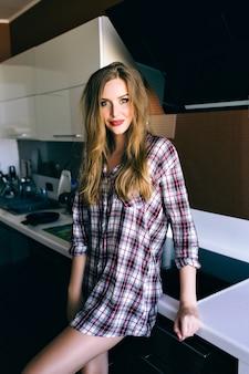 かなりブロンドの女性の屋内ライフスタイルの肖像画はリラックスして彼女の朝の時間を楽しんで、キッチンでポーズをとって、居心地の良い格子縞のシャツ、ビンテージフィルムの柔らかい色を着ています。