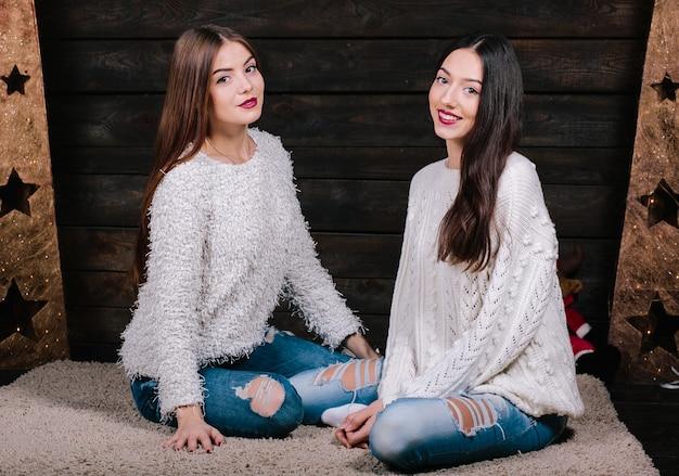 Крытый образ жизни портрет двух довольно молодых забавных женщин-друзей обнимает, улыбаясь и весело