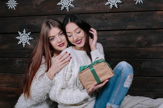 Крытый образ жизни портрет двух довольно молодых забавных женщин-друзей обнимает улыбку