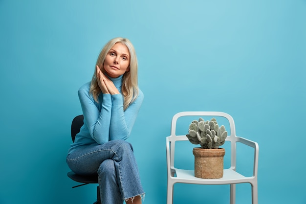 Indoor middle aged wrinkled woman feels bored and lonely keeps palms pressed together looks directly, poses near chair with cactus