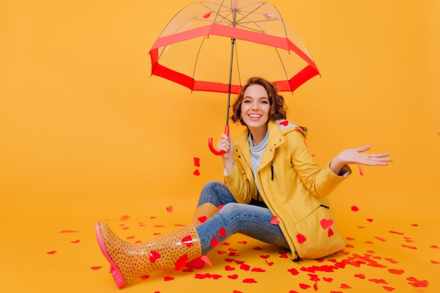 Indoor photo of beautiful girl in autumn attire laughing while posing on the floor with parasol. cute curly woman in jeans enjoying photoshoot in valentine's day.