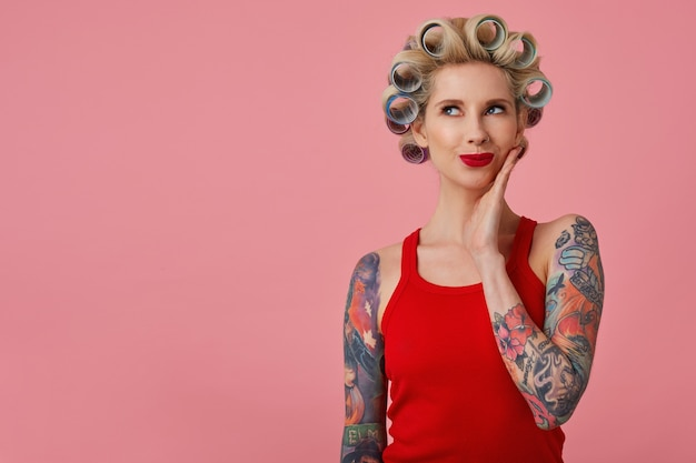 Indoor photo of beautiful positive young blonde lady with tattooes dressed in red shirt looking dreamily upwards with palm on her cheek, posing over pink background with curlers on her head