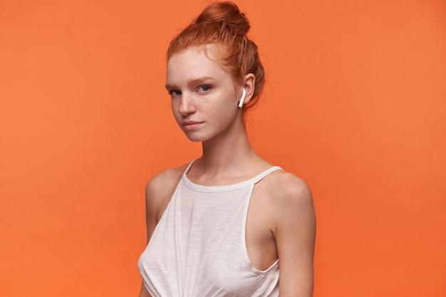 Foto interna di bella giovane femmina che indossa i suoi capelli rossi in nodo, indossa top bianco e auricolari, guardando la telecamera con la faccia calma, in posa su sfondo arancione