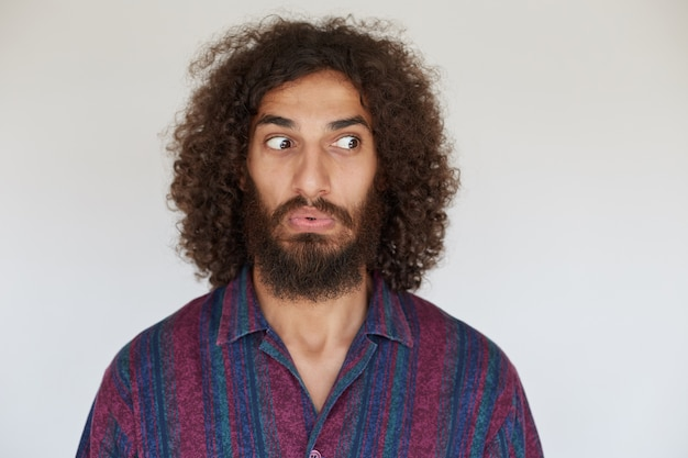 Indoor photo of bemused young brunette curly bearded male dressed in casual clothes folding lips and rounding eyes confusedly
