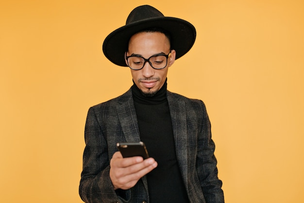 Indoor photo of black young man in gorgeous attire holding smartphone.emotional african guy waiting for call with smile.