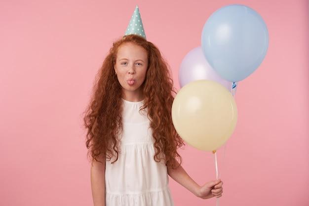Foto al coperto di una ragazzina rossa allegra con lunghi capelli ricci in piedi su sfondo rosa con mongolfiere, indossa un abito bianco e cappello di compleanno, sorride con gioia e mostra la lingua