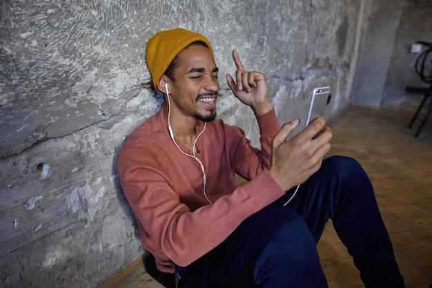 Foto interna di allegro giovane uomo dalla pelle scura con la barba che si appoggia sul muro di cemento mentre è seduto sul pavimento di legno, godendo di brani musicali sul suo telefono cellulare con gli occhi chiusi