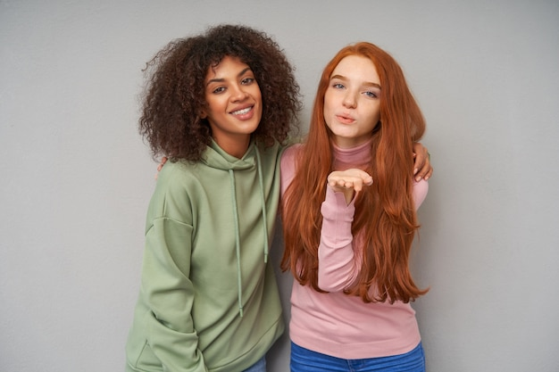 Indoor photo of cheerful young lovely girlfriends hugging each other while posing over grey wall in comfortable casual clothes, looking positively