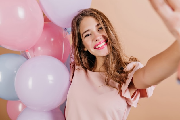 Indoor photo of cute woman with long hairstyle making selfie after birthday party