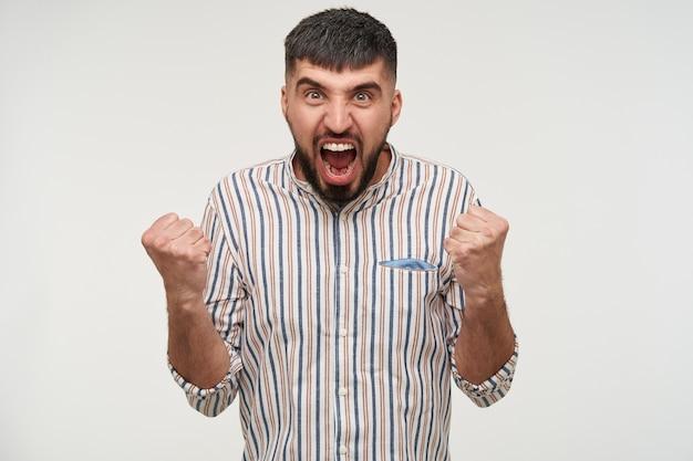 Foto al coperto di giovane maschio bruna eccitato che aggrotta le sopracciglia mentre urla febbrilmente con la bocca spalancata e tiene i pugni alzati, in piedi contro il muro bianco