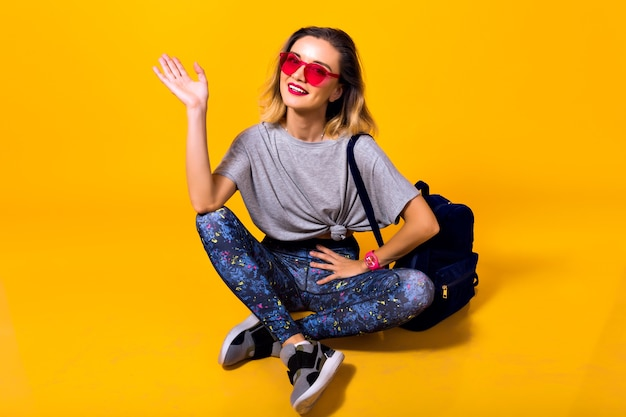 Indoor photo of girl in colorful leggings and trendy shirt sitting on the floor. studio portrait of stylish young woman in sport shoes posing on yellow background and holding backpack.