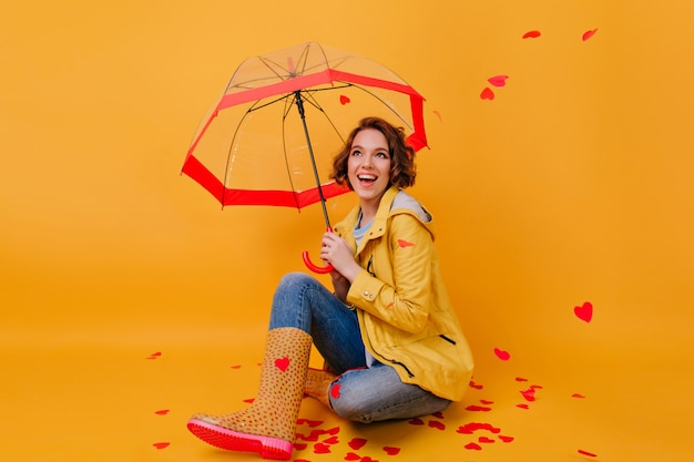 Indoor photo of girl in trendy rubber shoes laughing under umbrella. studio shot of ecstatic lady fooling around in valentine's day.