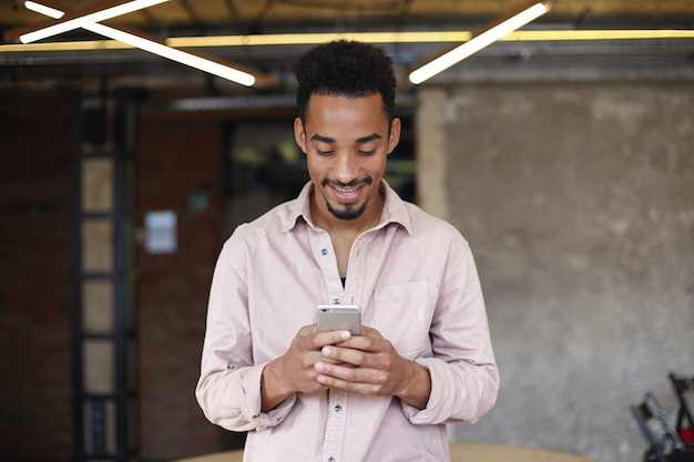 Indoor photo of handsome smiling dark skinned guy with beard standing over coworking space and holding smartphone, looking positively at screen while chatting with his friends