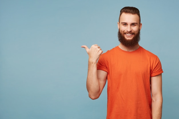 Indoor photo of happy delighted handsome bearded guy on blue