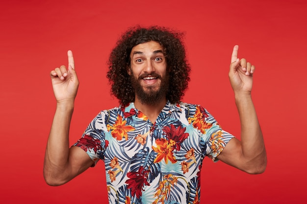 Indoor photo of happy young bearded male with long brown curly hair pointing upwards with forefingers, raising cheerfully eyebrows and smiling broadly, standing against red background