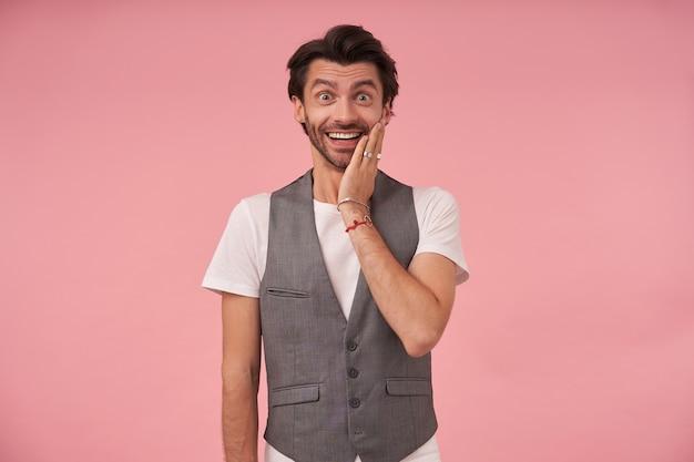 Foto al coperto di gioioso maschio barbuto con taglio di capelli alla moda che guarda l'obbiettivo con ampio sorriso, indossa un gilet grigio e una maglietta bianca, in piedi su sfondo rosa e tenendo il palmo sulla guancia