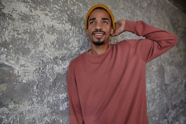 Indoor photo of lovely young bearded dark skinned male in casual clothes holding raised hand on his head and looking thoughtfully aside, standing over concrete wall