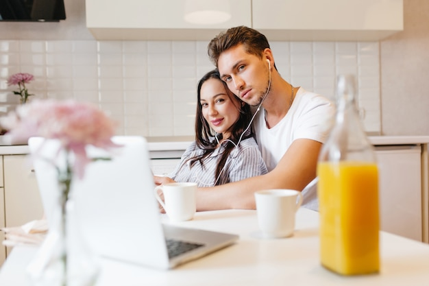 Foto dell'interno della coppia di innamorati utilizzando laptop, mentre ci si rilassa in cucina