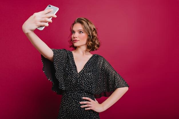 Claret 배경에 셀카를 만드는 빈티지 드레스에 매력적인 젊은 아가씨의 실내 사진