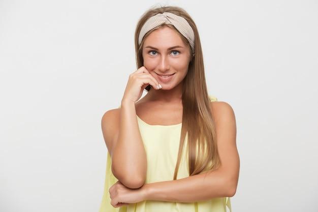 Фотография в помещении красивой позитивной молодой блондинки с естественным макияжем, нежно касающейся ее лица поднятой рукой и приятно улыбающейся, стоящей на белом фоне