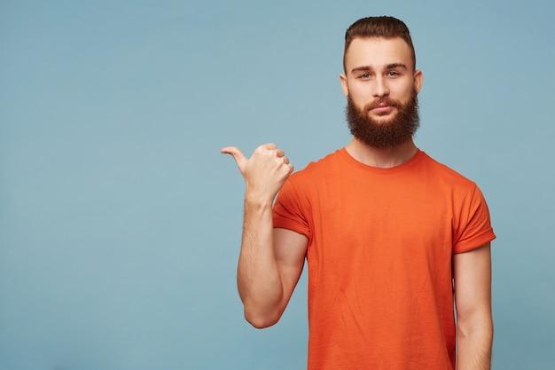 Фотография в помещении спокойного дружелюбного красивого бородатого парня, изолированного на синем