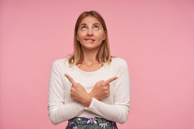 Фотография в помещении очаровательной симпатичной блондинки в белой блузке и юбке в цветочек, позирующей на розовом фоне со скрещенными руками, показывая в разные стороны указательными пальцами