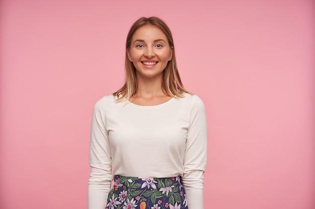 ピンクの背景の上に広い誠実な笑顔でポーズをとって、体に沿って手を保ち、彼女の白い完璧な歯を示す魅力的な若いブロンドの女性の屋内写真