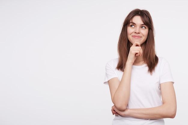 白い壁にポーズをとっている間カジュアルな服を着て、楽しい笑顔で彼女のあごに手を上げたままでいる陽気な若い素敵なブルネットの女性の屋内写真