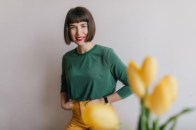 短い散髪ポーズで自信を持って女の子の屋内写真。前景に黄色いチューリップと陽気なブルネットの女性の肖像画。