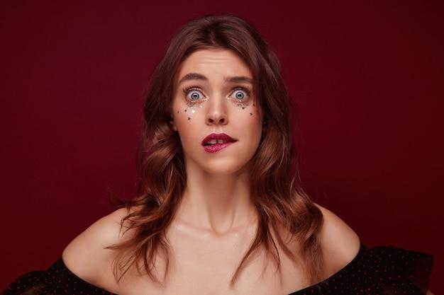 波状の髪型と彼女の顔に銀色の小さな星が驚いて見ていると下唇を噛んで混乱している若いブルネットの女性の屋内写真