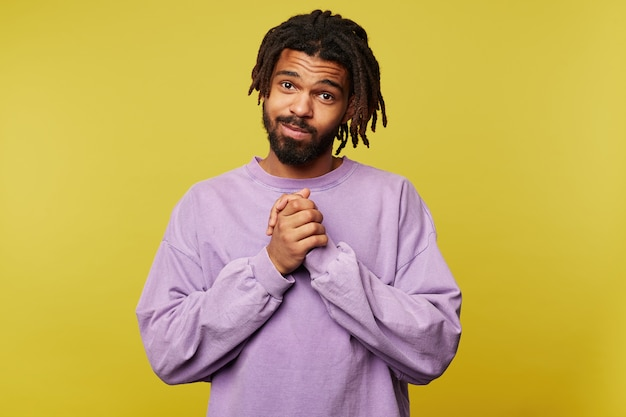 Фотография в помещении симпатичного молодого темнокожего брюнет с дредами, складывающего поднятые руки в благодарном жесте и приятно смотрящего в камеру, позируя на желтом фоне