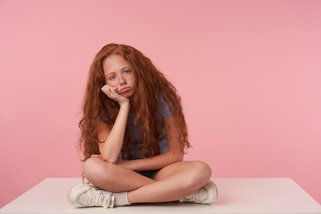 カジュアルな服装でピンクの背景の上に足を組んで座って、退屈な顔でカメラを見て、上げられた手に頭を傾けて巻き毛のセクシーな髪を持つ女性の子供の屋内写真