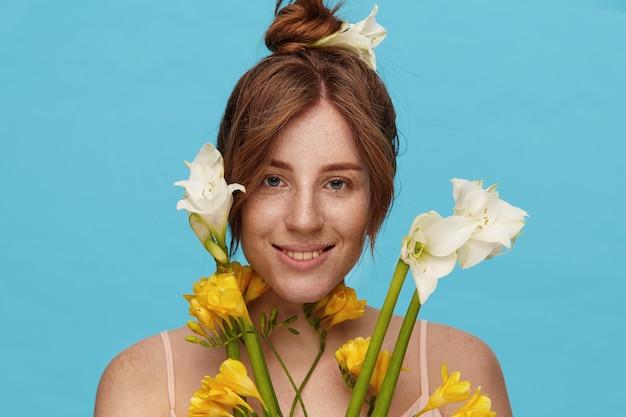 花の花束と青い背景の上に立っている間楽しい笑顔でカメラを見ているパンの髪型を持つ嬉しい若い赤毛の女性の屋内写真