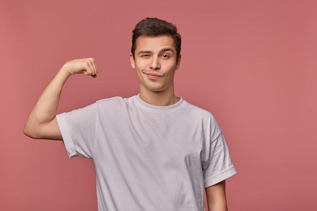 짧은 머리가 회색 티셔츠에 분홍색 배경 위에 서서 손을 들고 그의 힘을 보여주는 잘 생긴 젊은 남성의 실내 사진, 교활하게 카메라를보고 눈썹을 올리는