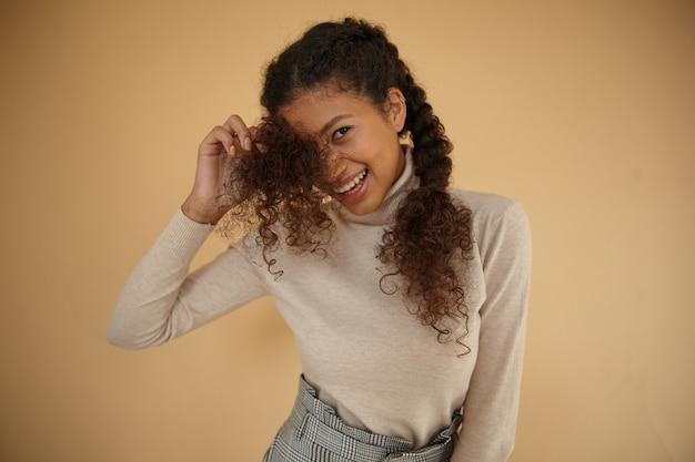 베이지 색 배경 위에 서서 좋은 분위기에 진심으로 웃고있는 동안 롤 넥 모직 스웨터를 입고 곱슬 꼰 머리를 가진 사랑스러운 젊은 어두운 피부 갈색 머리 아가씨의 실내 사진