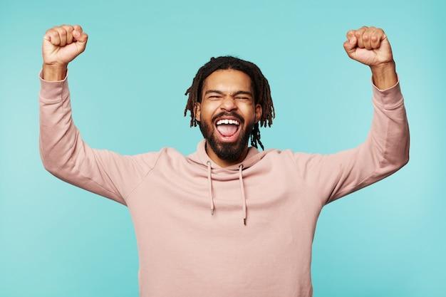 青い背景の上に立って、何かについて喜んでいる間、幸せな手を上げて暗い肌を持つ大喜びの若い魅力的なブルネットの男の屋内写真