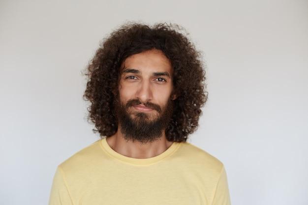 カジュアルな服を着て、ポーズをとって少し笑っている茶色の巻き毛の心地よい見た目のポジティブな若いひげを生やした男の屋内写真