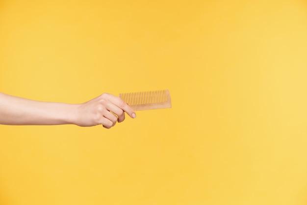 Фотография в помещении руки красивой женщины, протягивающейся вперед, держа деревянную расческу, изолированную на оранжевом фоне. человеческие руки и концепция языка тела