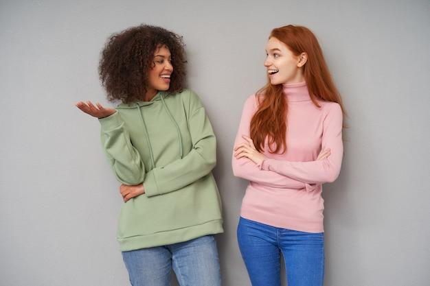 Фотография в помещении, на которой довольно позитивные молодые подружки весело смотрят друг на друга с приятной улыбкой, делясь новостями, в повседневной одежде и позируют на серой стене
