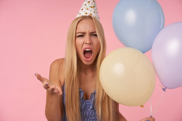 怒って手のひらを上げ、口を大きく開けてカメラを見て、悪意を持って、ヘリウム気球の束でピンクの背景の上にポーズをとって深刻な若いブロンドの女性の屋内写真