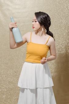 Внутреннее фото тонкой женской модели, держащей бутылку.