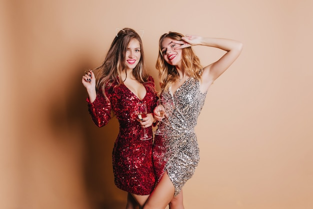두 즐거운 여성의 실내 사진은 샴페인을 마시고 크리스마스 파티 동안 장난