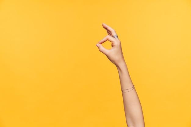 Фотография в помещении ухоженных, светлокожих женских рук с поднятыми орнаментами, показывая жест пальцами ок, изолированные на желтом фоне