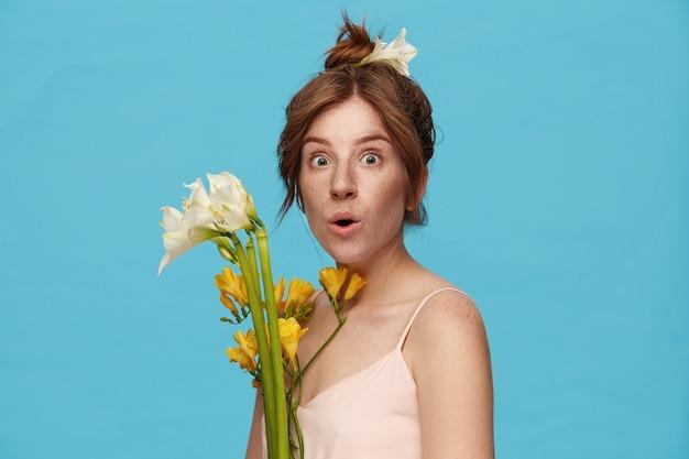 青い背景の上に立っている間花の花束を持って、カメラを見ながら驚いて彼女の緑の目を丸める若い興奮した赤毛の女性の屋内写真