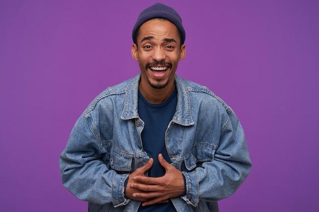 Фотография в помещении молодого привлекательного темнокожего брюнет с бородой, хватающегося руками за живот, радостно смеющегося и радостно смотрящего, изолированного над фиолетовой стеной