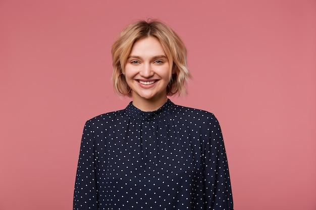 Фотография в помещении молодой красивой привлекательной блондинки, одетой в блузку в горошек, с радостным выражением лица, показывающая позитивный, улыбающийся, счастливый, изолированный