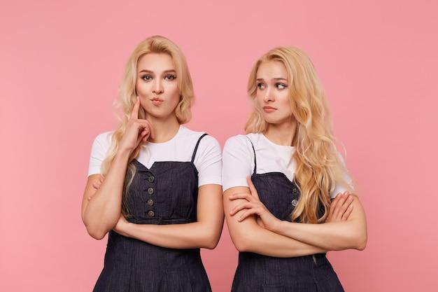 カメラを注意深く見ながら人差し指を上げたままの若い茶色の目の長い髪の女性の屋内写真、彼女の混乱したかわいいブロンドの妹とピンクの背景の上にポーズをとる