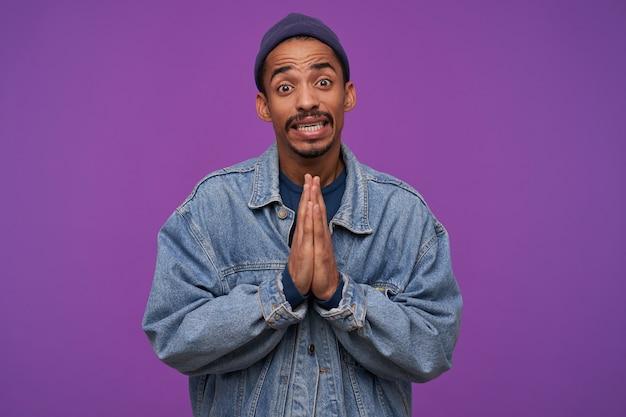 젊은 어두운 피부 수염 갈색 머리 남자의 실내 사진은 보라색 벽 위에 포즈를 취하는 동안 제스처를기도하면서 손을 올리며, 이마를 주름지고 보는 동안 이빨을 보여주는